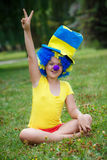 Funny girl in clown wig with blue nose Royalty Free Stock Photography