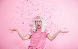 Funny Girl con el pelo de plata da una sonrisa y una emoción en fondo rosado Mujer joven o muchacha adolescente con confeti foto de archivo