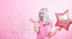Funny Girl con el pelo de plata da una sonrisa y una emoción en fondo rosado Mujer joven o muchacha adolescente con los globos y  foto de archivo libre de regalías