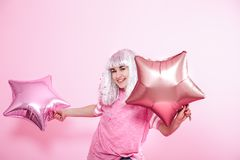 Funny Girl con el pelo de plata da una sonrisa y una emoción en fondo rosado Mujer joven o muchacha adolescente con los globos y  fotografía de archivo