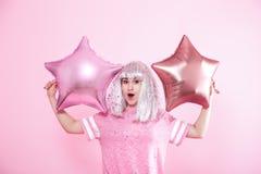 Funny Girl con el pelo de plata da una sonrisa y una emoción en fondo rosado Mujer joven o muchacha adolescente con los globos y  imágenes de archivo libres de regalías
