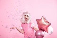 Funny Girl con el pelo de plata da una sonrisa y una emoción en fondo rosado Mujer joven o muchacha adolescente con los globos y  fotos de archivo