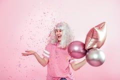 Funny Girl con el pelo de plata da una sonrisa y una emoción en fondo rosado Mujer joven o muchacha adolescente con los globos y  imagen de archivo