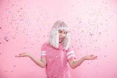 Funny Girl con el pelo de plata da una sonrisa y una emoci?n en fondo rosado Mujer joven o muchacha adolescente con confeti fotos de archivo libres de regalías