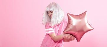 Funny Girl con el pelo de plata da una sonrisa y una emoci?n en fondo rosado Mujer joven o muchacha adolescente con los globos y  fotos de archivo