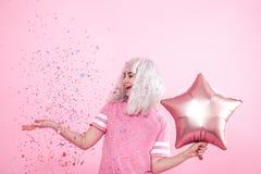 Funny Girl con el pelo de plata da una sonrisa y una emoci?n en fondo rosado Mujer joven o muchacha adolescente con los globos y  imagen de archivo libre de regalías