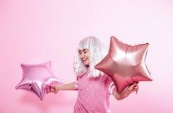 Funny Girl con el pelo de plata da una sonrisa y una emoci?n en fondo rosado Mujer joven o muchacha adolescente con los globos y  imágenes de archivo libres de regalías