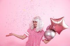 Funny Girl con el pelo de plata da una sonrisa y una emoci?n en fondo rosado Mujer joven o muchacha adolescente con los globos y  imagen de archivo