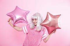 Funny Girl con el pelo de plata da una sonrisa y una emoci?n en fondo rosado Mujer joven o muchacha adolescente con los globos y  fotografía de archivo libre de regalías