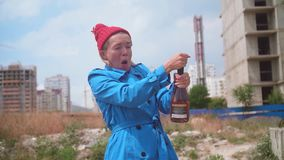 Funny girl on a construction site. The blonde dressed in a blue coat, red hat in the summer, opens champagne. Funny girl on a construction site on a sunny stock footage