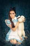 Funny Girl Costumed as Alice in Wonderland with The White Rabbit. Portrait of a surprised girl in a blue costume holding a white bunny Stock Image