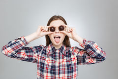 Funny girl covered her eyes with candies and showing tongue Royalty Free Stock Image