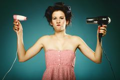 Funny girl in curlers with hairdryer styling hair Royalty Free Stock Image