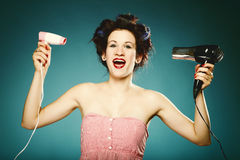 Funny girl in curlers with hairdryer styling hair Stock Photo