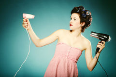 Funny girl in curlers with hairdryer styling hair Stock Photography