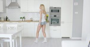 Funny girl dancing in kitchen stock video
