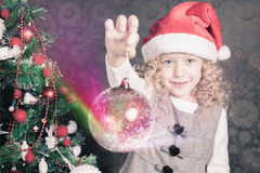 Funny girl decorating a christmas tree Stock Photos