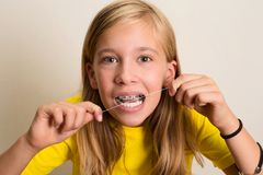 Funny girl with dental braces flossing her teeth. Close-up portrait of pre teen girl with dental floss isolated.