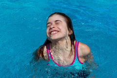 Funny girl dives and comes up to the surface of the swimming poo royalty free stock photography