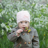 Funny girl with Down syndrome in the mouth pulls dandelions. Funny girl with Down  syndrome in the mouth pulls dandelions Stock Image
