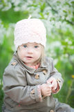 Funny girl with Down syndrome in the mouth pulls dandelions Royalty Free Stock Photo