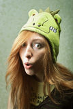 Funny girl in dragon hat Stock Images