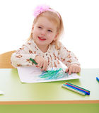 Funny girl draws with markers sitting at the table Stock Photography