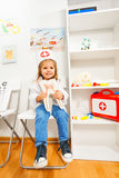 Funny girl dressed as a dentist at medical room. Funny little girl dressed as a dentist holding tooth model at the medical room Royalty Free Stock Photo