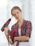 Funny girl with a drill drills head. Funny beautiful girl with a drill drills head royalty free stock photography
