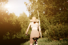 Funny girl driving bicycle outdoor. Sunny summer lifestyle concept. Woman in dress and hat in Field with dandelions Stock Photo