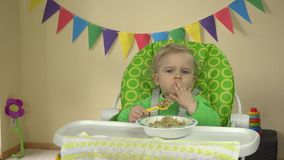 Funny girl eat porridge with spoon and hands sitting in baby feeding chair. stock footage