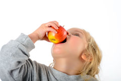 Funny girl eating apple royalty free stock photography