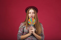 Funny girl eating big striped lollipop Royalty Free Stock Photos