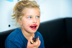 Funny girl eating bread roll with marmelade Stock Images