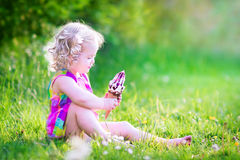 Funny girl eating ice cream in sunny garden Royalty Free Stock Images
