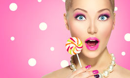 Funny girl eating lollipop. Over pink polka dots background stock photos