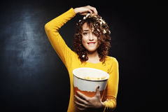 Funny girl eating popcorn while watching shows at home party. Popcorn on head and hair Royalty Free Stock Images
