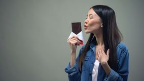 Funny girl enjoying sweet aroma of chocolate bar, kissing it, woman keeping diet. Stock footage stock video footage