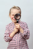 Girl explores with a magnifying glass. Royalty Free Stock Images