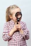Girl explores with a magnifying glass. Stock Image