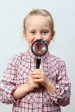 Girl explores with a magnifying glass. Royalty Free Stock Photo