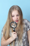 Girl explores with a magnifying glass. Royalty Free Stock Image