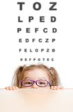 Funny girl in eyeglasses with eye chart royalty free stock image