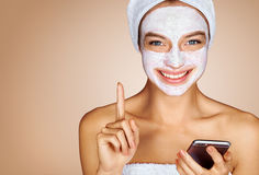Funny girl with facial mask using smartphone. Photo of attractive young woman receiving spa treatments. Beauty & Skin care concept Royalty Free Stock Photo