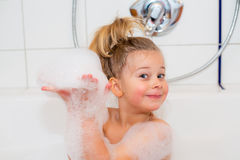 Funny girl with foam bathtub in the bathtub Stock Photo