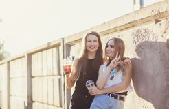 Funny girl friends. Holding a glass of juice in the city royalty free stock photos