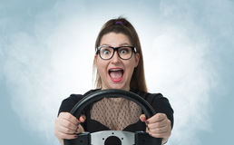 Funny girl in glasses with car wheel and white smoke, auto concept. Funny girl in glasses with car wheel and white smoke on background, auto concept royalty free stock image