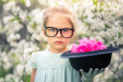 Funny girl in glasses with hat and gloves. Funny girl in glasses and gloves and with hat playing in spring garden stock photos