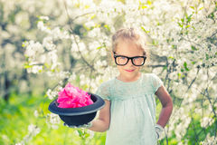 Funny girl in glasses with hat and gloves. Funny girl in glasses and gloves and with hat playing in spring garden royalty free stock photo
