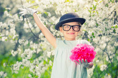 Funny girl in glasses with hat and gloves. Funny girl in glasses, hat and gloves playing in spring garden stock photo